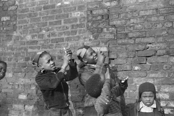 CHICAGO: CHILDREN, 1941.   Boys playing and pretending that they are shooting machine guns at a passing airplane, on the South Side of Chicago, Illinois. Photograph by Edwin Rosskam, April 1941