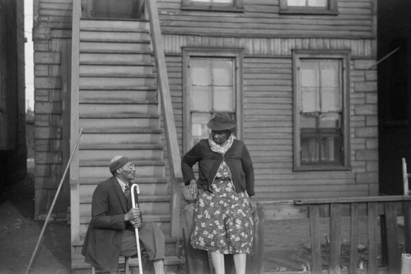 CHICAGO: CONVERSATION, 1941.   Two African American woman talking outside of an apartment building on the South Side of Chicago, Illinois. Photograph by Edwin Rosskam, April 1941