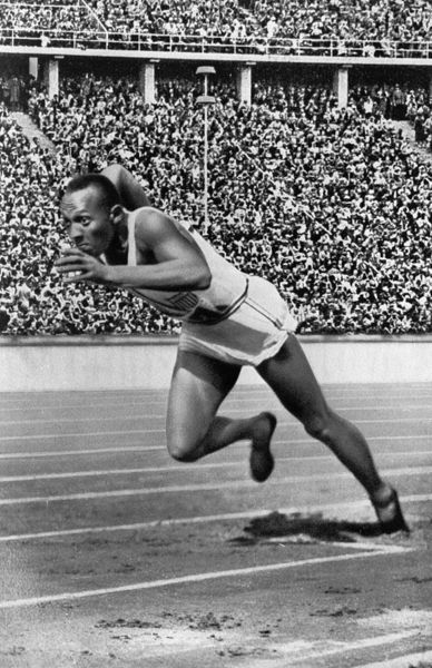 JESSE OWENS (1913-1980).  American athlete. Photographed at the Olympic Games in Berlin, 1936, at the start of the 200 meter sprint final, which he won, setting an Olympic record