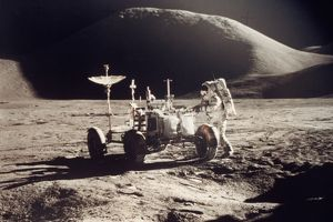 APOLLO 15, 1971. Jim Irwin standing by the lunar rover, Mount Hadley in the background.