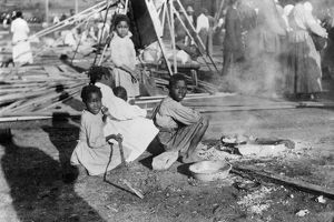 FLOOD REFUGEES, 1912. Refugees from a flood in Louisiana cooking government rations