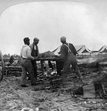 GALVESTON HURRICANE, 1900. Relief workers carrying a dead body to be burned in Galveston