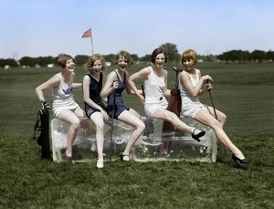 GOLFING, 1926. Women wearing bathing suits, sitting on a block of ice on a golf course