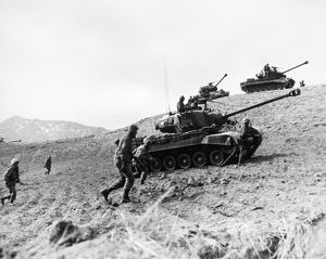 KOREAN WAR: INFANTRYMEN. American Infantrymen supported by tanks advance up a hill in Korea