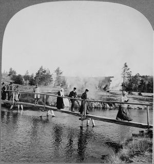 YELLOWSTONE: TOURISTS, c1904. Tourists walking across a footbridge among the geysers