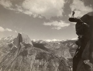 YOSEMITE VALLEY, c1901. A man standing on a overhanging rock facing Half Dome at